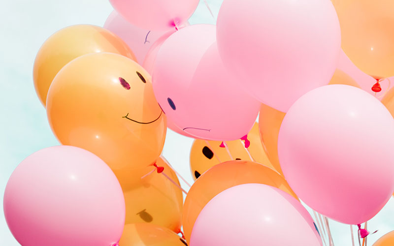 Picture of a bunch of balloons with some smiling and some frowning