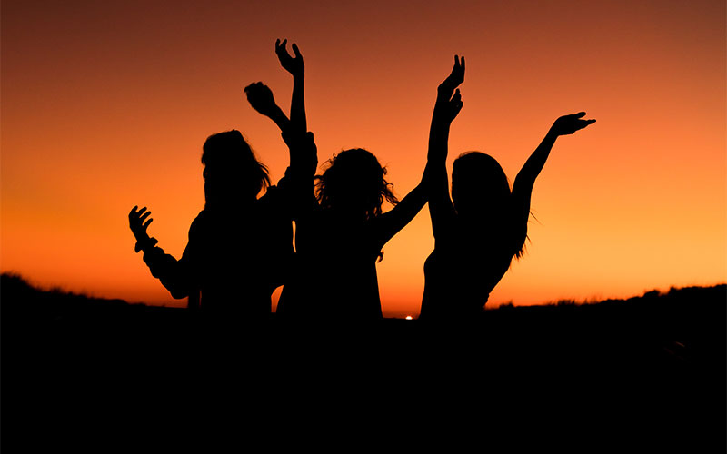 Picture of girls dancing with the sunset as a backdrop