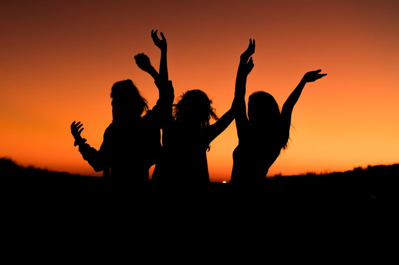 Silhouette of three girls dancing at sunset.