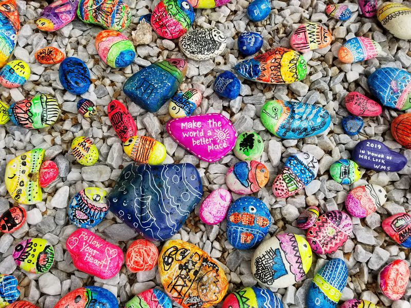 Colourful pebbles on the beach with writing on them