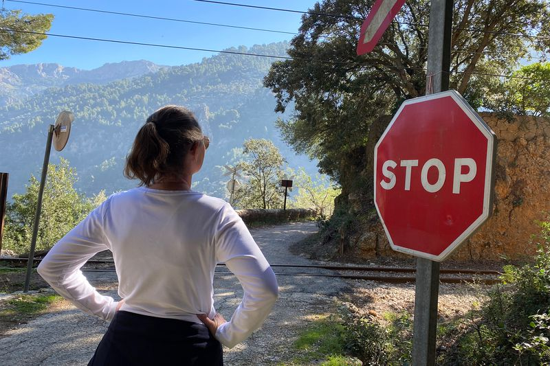 Picture of Tiffany Barnard waiting for a train at a stop sign.